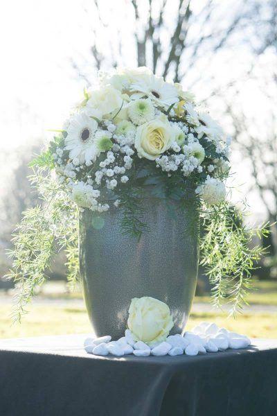 Urne mit Dekoration und aufgesetztem Blumengesteck